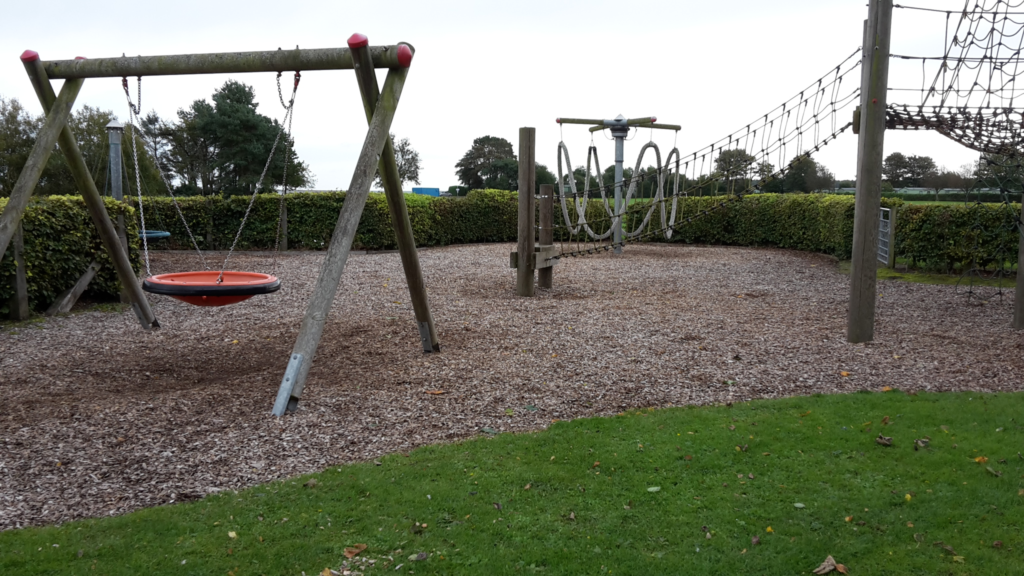 Play area with swing, cargo net and other play equipment on ground covered with wood chips and surrounded by hedges