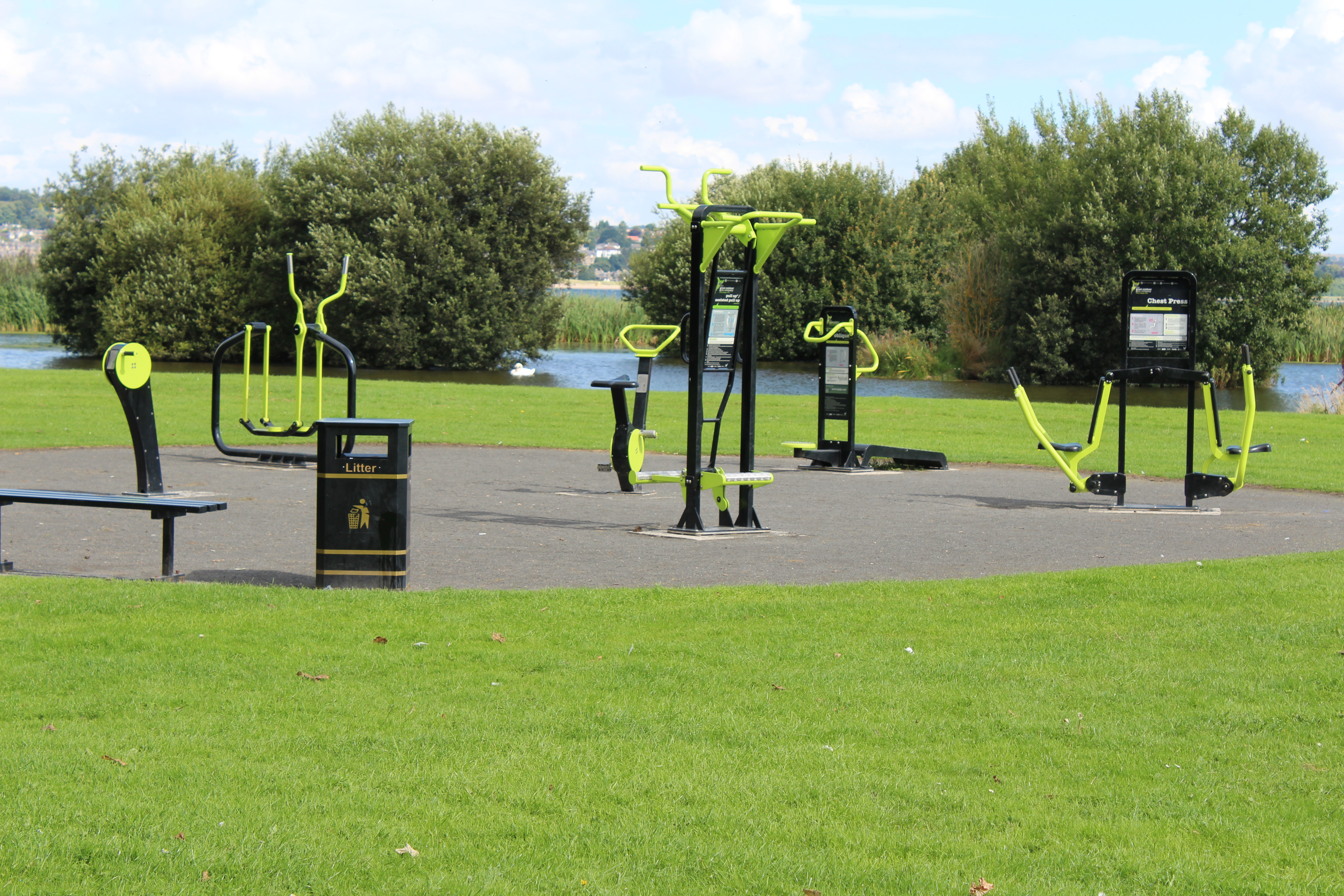 The outside gym on a sunny day, the pond can be seen in the background.
