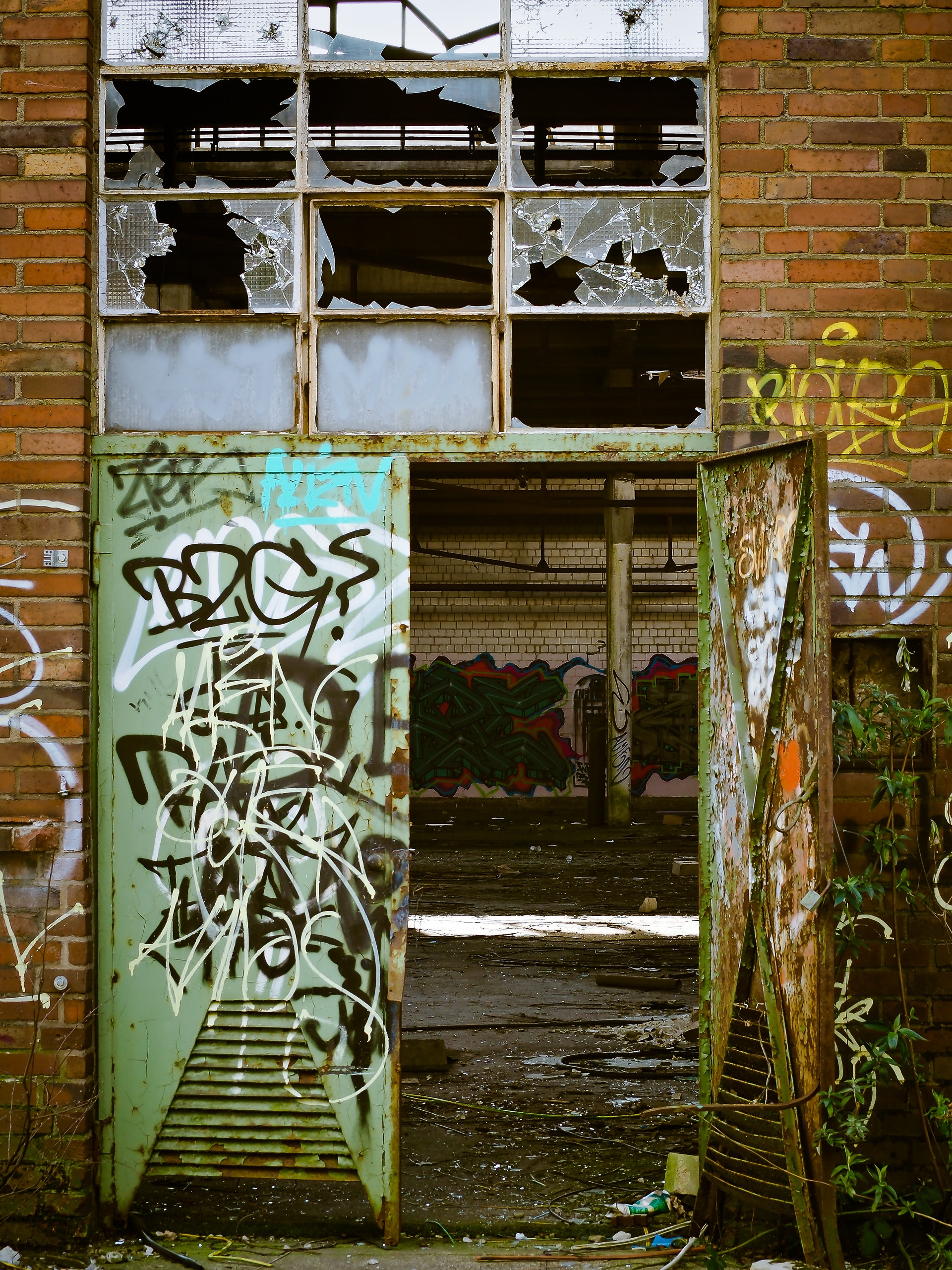photo of building with broken windows and graffiti